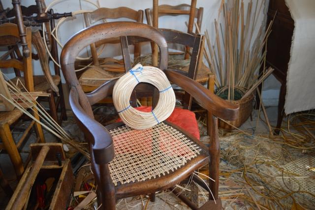 Chaise haute en pleine restauration en cannage par le maitre rempailleur de chaise